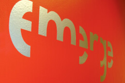Photograph of Emerge logo on red wall